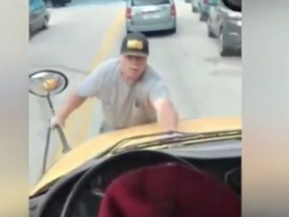 Video shows irate man clinging to front of Maryland school bus