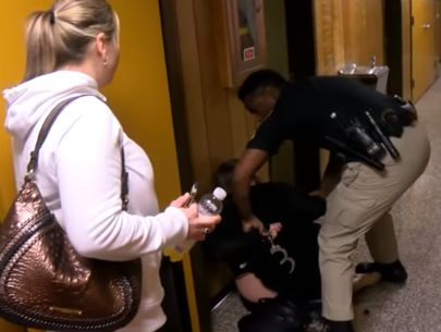Teacher handcuffed after questioning superintendent's raise during school board…