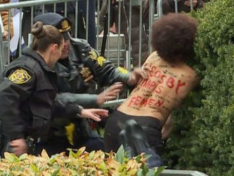 Topless protester at Cosby trial jumps barricade, tackled by police
