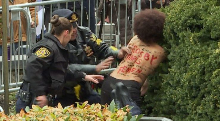 Topless protester at Cosby assault trial jumps barricade, tackled by police